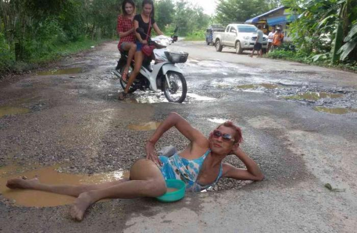 Man 'bathes' in pothole to push road repairs | The Thaiger